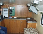 """Управление печкой (как и всё другое стандартное оборудование спрятано в шкафчики). Открыт холодилник """"Электролюкс"""", 70 литров работает как от сети 12/220 В, так и на газу. Стол сложен."""